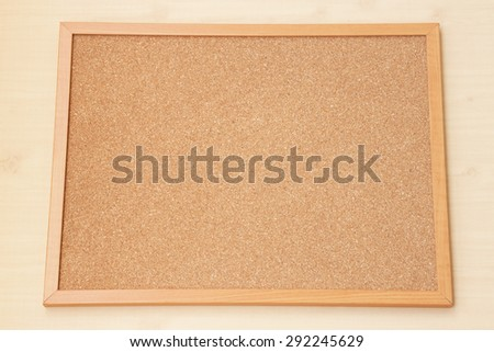Blank Cork board with wooden frame on wooden floor.