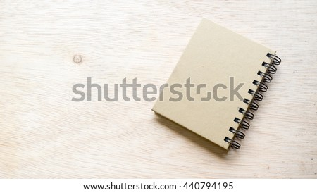 Blank cover notepad or memo pad diary book on wooden surface. Isolated on an empty background. Slightly de-focused and close-up shot. Copy space. - stock photo