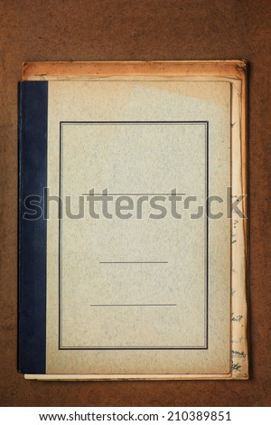 Blank cover of an old grungy note book on old wooden desk.   - stock photo