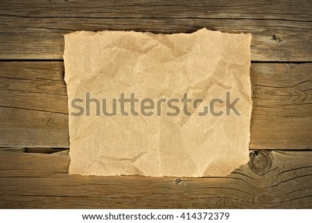 Blank crumbled brown paper on a rustic wooden background - stock photo