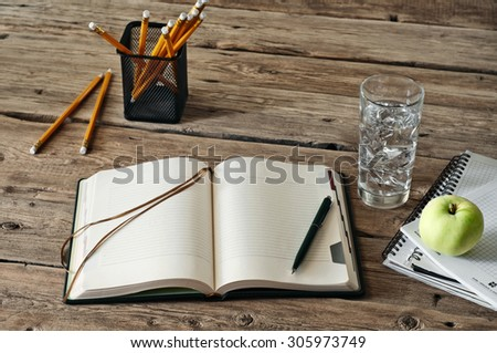 blank diary on wooden table with a glass of water, apple and pencil closeup. Free space for text. Copy space - stock photo