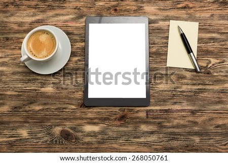 Blank. Digital tablet computer with sticky note paper and cup of coffee on old wooden desk. Simple workspace or coffee break with web surfing. - stock photo