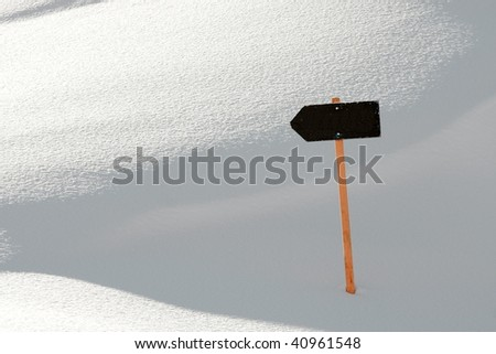 Blank direction sign in the fresh, untouched snow - stock photo