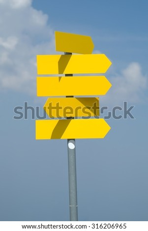 Blank direction signs against clear blue sky - stock photo
