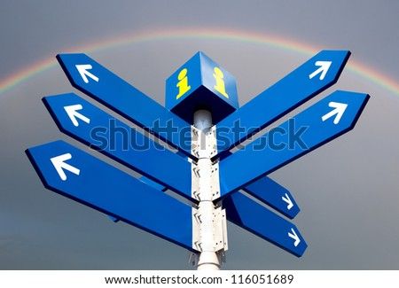 Blank directional road signs over rainbow - stock photo