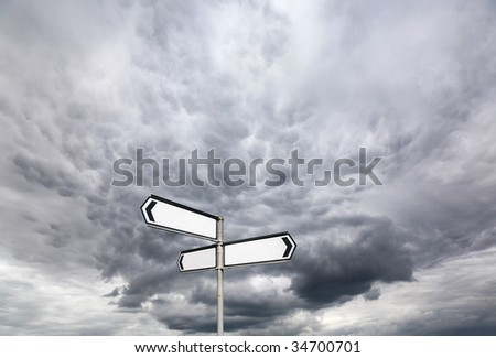 Blank Directional Sign Post against a dramatic Sky - stock photo