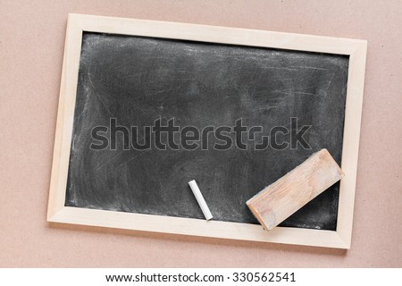 Blank dirty blackboard , chalk and eraser on wood background