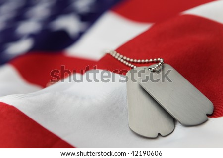 Blank dog tags on American flag with focus on tags - Shallow dof - stock photo