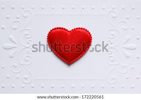 Blank embossed white paper with red satin hearts on it.   - stock photo