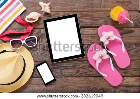 Blank empty tablet computer on the beach. Trendy summer accessories on wooden background pool. Sunglasses, orange juice and flip-flops on beach. Tropical flower orchid. Flat mock up for design. - stock photo