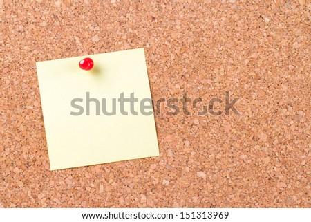 Blank, empty, yellow sticky post it pinned on cork bulletin board with red pin, ready for your message.