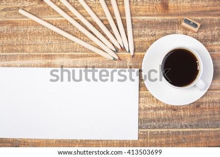Blank envelope, coffee, pencils and sharpener on wooden desktop. Topview, Mock up - stock photo