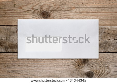 Blank envelope with address window on wooden table - stock photo