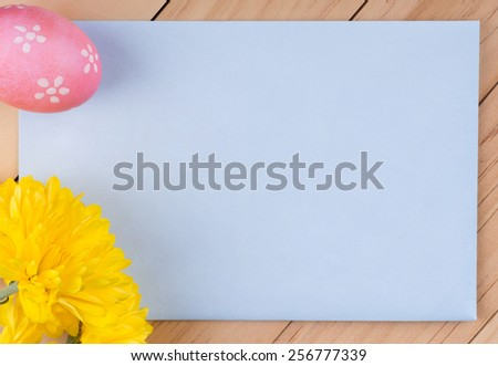 Blank envelope with decorated Easter egg and flower - stock photo