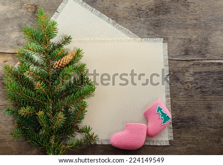 Blank fabric with space for text decorated with branch of christmas tree and tiny pink felt boots at wooden background - stock photo