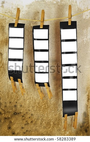 blank film strips, against grungy background, empty frames, free picture or copy space - stock photo