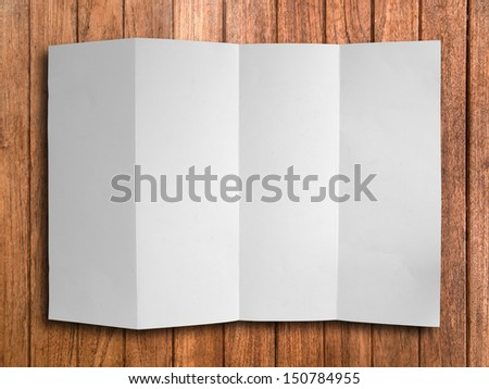 Blank Fold White Paper on Wood Background With Shadow - stock photo