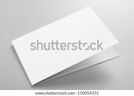 Blank folded card over grey background with shadow - stock photo