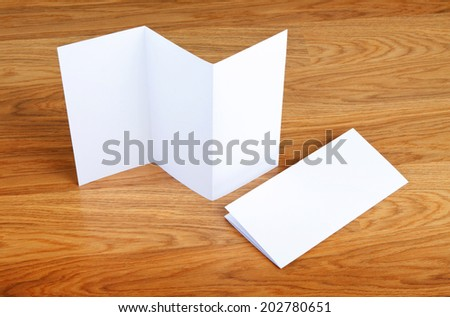 Blank folding page booklet on wooden background - stock photo
