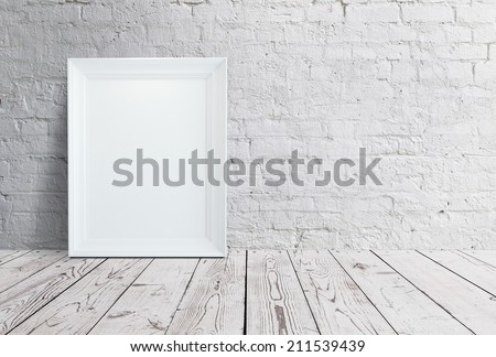 blank frame hanging on brick wall - stock photo