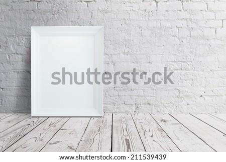 blank frame hanging on brick wall - stock photo