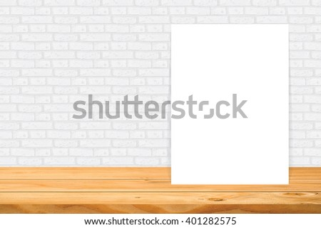 Blank frame on wooden table at white tile wall,Template mock up for adding your design and leave space beside frame for adding more text. - stock photo