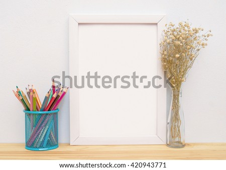 Blank frame, pencil and flower on the table, mock up