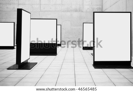 Blank frames shown in concrete room. - stock photo