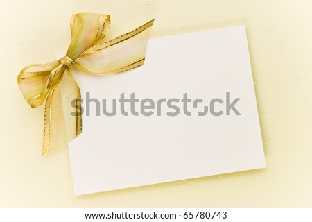 Blank gift tag tied with a bow of gold satin ribbon on paper. Natural texture - stock photo