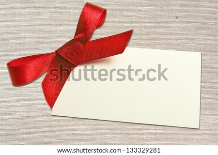 Blank gift tag tied with a bow of red satin ribbon. - stock photo