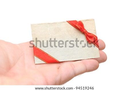 blank gift tag with red ribbon and bow in hand holding on white