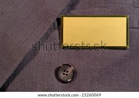 Blank gold and brass name tag on corporate business man suit jacket breast pocket with empty copy space for text insertion - stock photo