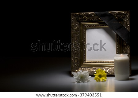 blank golden mourning frame with flowers and candle on dark background - stock photo
