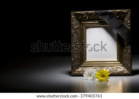 blank golden mourning frame with flowers on dark background  - stock photo