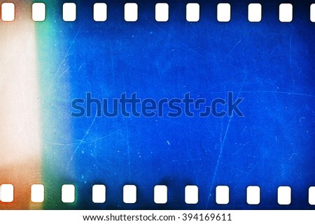 Blank grainy film strip texture background with lots of dust, noise and light leak - stock photo