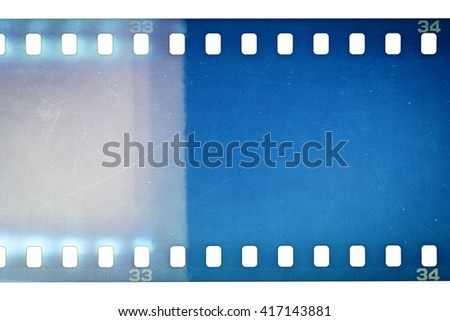 Blank grainy film strip texture background with lots of dust, noise and light leak isolated on white