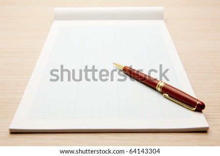Blank graphing paper pad and pen isolated on white. - stock photo