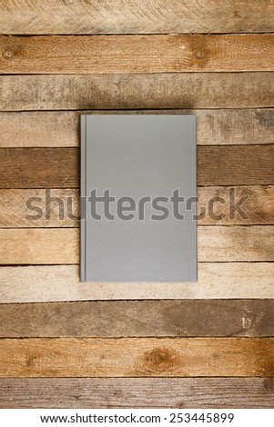 Blank gray book cover on wooden texture. Top view  - stock photo