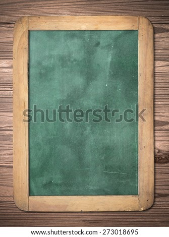 Blank green board on wood background. - stock photo