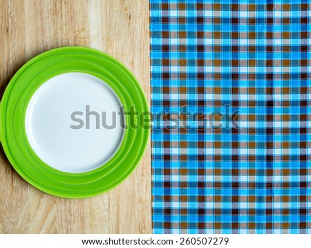Blank green plate on wooden table and checked tablecloth background - stock photo