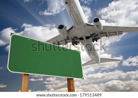 Blank Green Road Sign and Airplane Above with Dramatic Blue Sky and Clouds. - stock photo