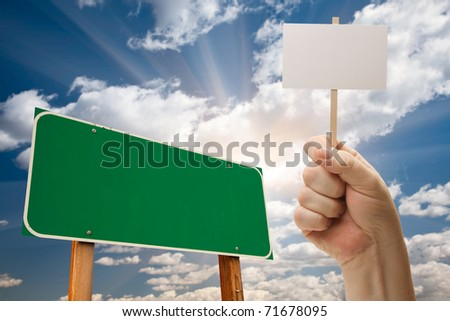 Blank Green Road Sign and Man Holding Poster on Stick Over Blue Sky and Clouds. - stock photo