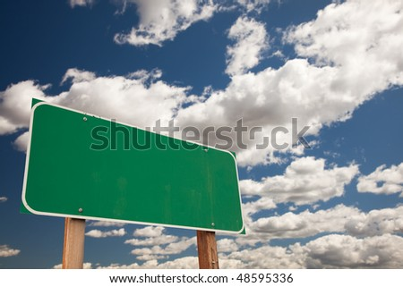 Blank Green Road Sign on Dramatic Blue Sky with Clouds - Plenty of Room For Your Own Text in the Clouds and on the Large Sign. - stock photo