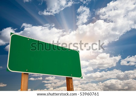 Blank Green Road Sign over Dramatic Blue Sky with Clouds and Sunburst - Ready for your own message and Room For Copy on Clouds. - stock photo