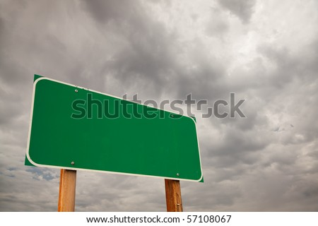 Blank Green Road Sign over Dramatic Stormy Clouds - Ready for your own message and Room For Copy on the Clouds. - stock photo