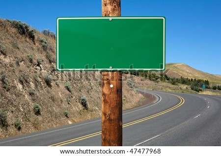 Blank green traffic sign on wooden electric pole against winding road - stock photo