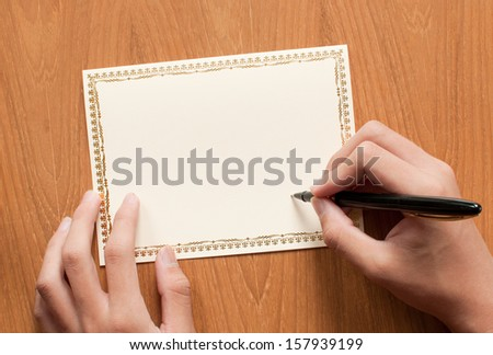 blank greeting card with hand and pen, writing - stock photo