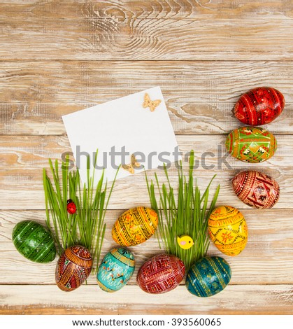 Blank, greeting easter card with easter eggs and green grass on shabby wooden background. - stock photo
