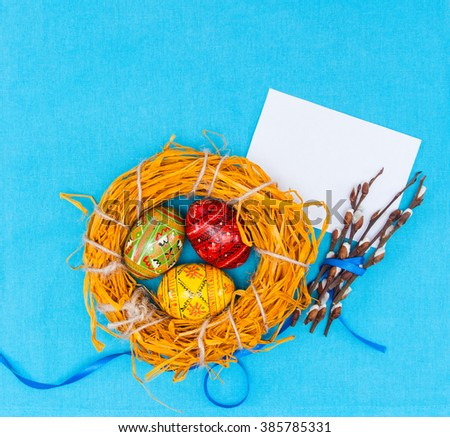 Blank, greeting easter card with handmade easter eggs, in nest,catkins.textile blue background - stock photo