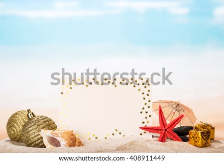 Blank greeting, sea shells and a star, Christmas toys, gifts in the sand against the sea. - stock photo